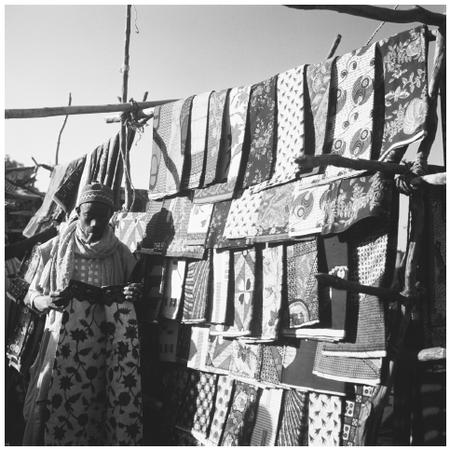 A man sells patterned cloth at a market. Nigerians are expert dyers, weavers, and tailors.
