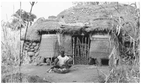 A man sits in front of his farmhouse in Toro, Nigeria. Traditionally, only men own land.