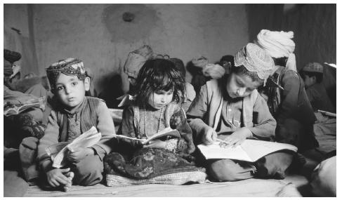 A group of children read in a mosque school in Arghandab, Afghanistan. Although education is valued in Afghanistan, only 5 percent of Afghani children receive a primary education.