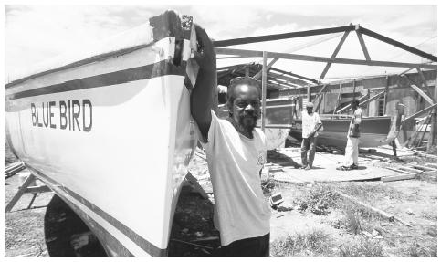 Shipwright David Hodge, known for building some of the fastest boats in Anguilla, stands by one of the boats he has built by hand.