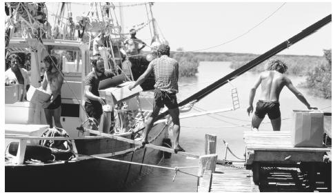 A traditional pearling lugger is loaded with supplies at Streeter's Jetty.