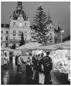 Customers explore the shops in the open-air Christmas Market at Hauptplatz in Graz.