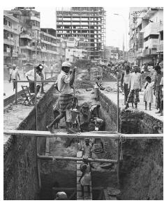 Road workers undertake construction work in Decca. Laborers make up the vast majority of workers in urban areas.