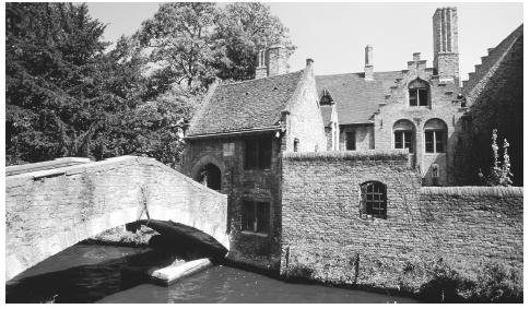 A stone bridge crossing a canal in Bruges. The north part of Belgium consists of isolated farms between villages, while the south tends to contain larger groups of farms.