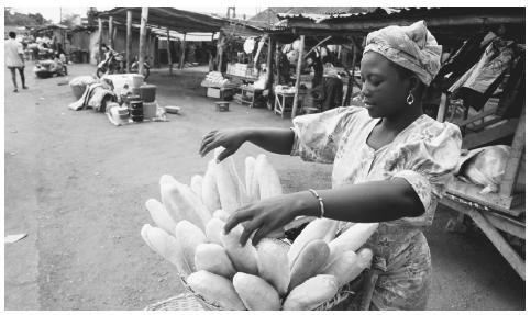 A woman selling baguettes at a market in Cotonou. Many Beninese homes lack refrigeration, necessitating almost daily trips to the marketplace.