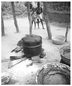 This Benin village cooks food communally in a large pot. Most cooking is done outdoors, even in urban areas.