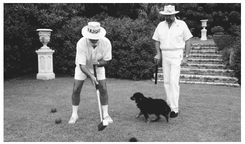 Two men playing croquet. Bermuda is an Overseas Territory of the British Crown.