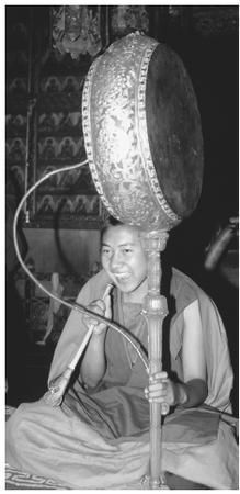 A young monk playing a drum. The national religion is the Vajrayana form of Mahayana Buddhism.