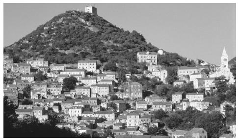 Stone houses with terracotta roofs cover a hill in the town of Lastovo on the island of Lastovo.