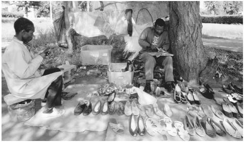 A man repairs shoes in the street in Gaborone, Botswana.