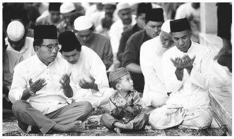 A young boy watches the adults as they perform the noon prayer at a mosque in Bandar Seri, Begawan. The Shafeite sect of Islam is the national religion.