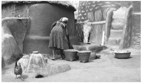 A Burkinabè woman sweeping her compound kitchen. Men and women have equal responsibilties in the agricultural sector of rural areas.