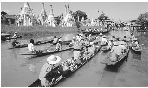 Small boat traffic on Lake Inle. Men are primarily responsible for the transportation of commercial goods.