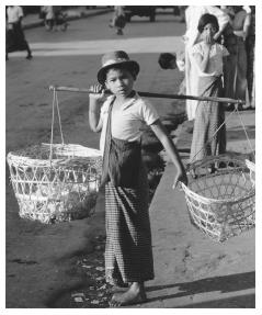 A child carrying baskets on a shoulder pole. Traditionally, all boys of eight to ten years of age attended school in a Buddhist monastery.