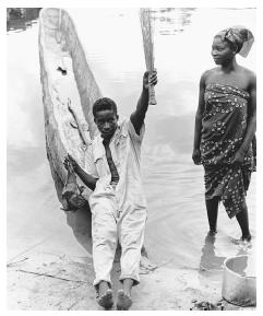 A boatman brings home a bat for soup to the banks of the Ubangi River in his dugout canoe. His wife wears a traditional print wrap dress.
