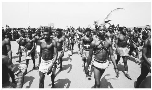 Men march in traditional dress to celebrate the coronation of Emperor Bokassa I.
