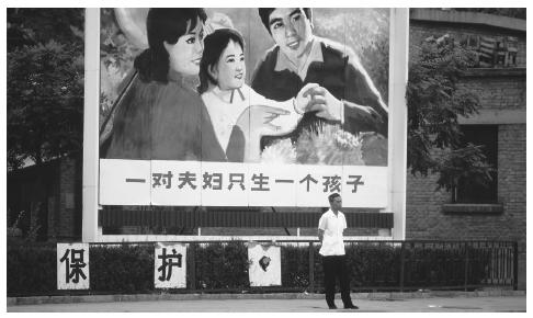 A man stands in front of a family planning billboard in Beijing. Due to China's huge population, most families are allowed to have only one child.