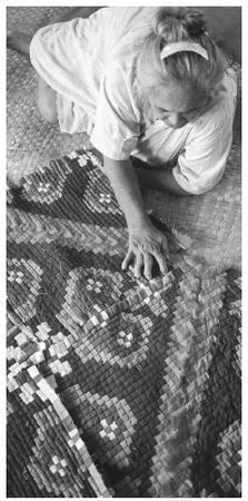 A woman sits on the floor making a colorful quilt in the city of Aitutaki.