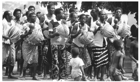 At the funeral of Nanan Toto Kra, a Baoule Akan, Mossi men dance with calabash rattles. Funerals, held 40 days after death, are important and elaborate ceremonies for Ivoirians.