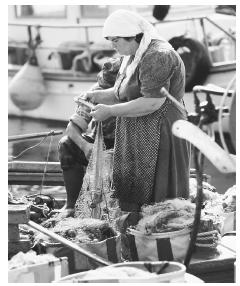 A man and woman repair fishing nets in a boat in Paphos, Cyprus.
