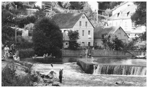 People relax by the river in the picturesque town of Rožmberk.