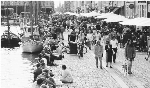 Crowds of tourists and Copenhagen residents mingle along the Stroget, a mile-long pedestrian street along the harbor.
