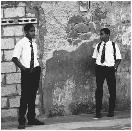 Uniformed schoolboys wait for the bus in Roseau. Opportunities for education after age fifteen are limited.