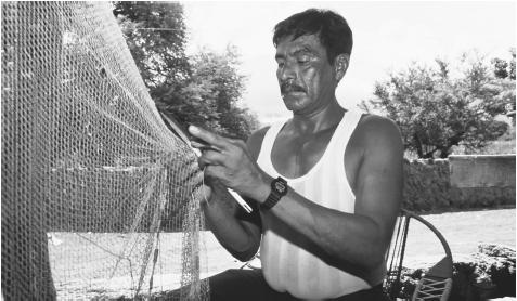 "A Salvadoran man works on his fishing net. Many Salvadorans are employed in low-paying, ""informal economy"" jobs."