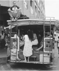 A passenger rides on top of the Papeete bus in Tahiti. Papeete is the only urban center in French Polynesia.