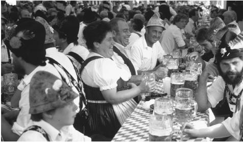 People socializing at a festival in Allgau. German beer, a favorite beverage, must be made only of water, hops, and malt.