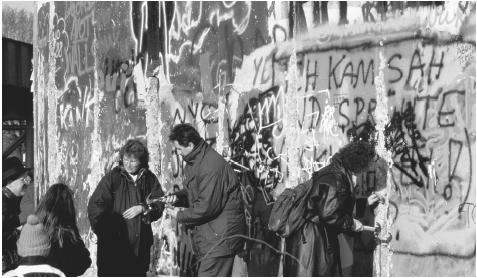 People collecting pieces of the Berlin Wall in 1989. Built in 1961, the wall was a visible reminder of Germany's defeat in World War II and subsequent division into first four, then two distinct and independent zones.