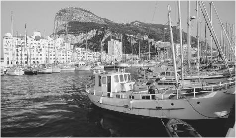 Fishing boats fill the harbor below the Rock of Gibraltar.