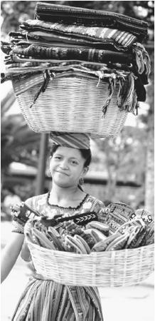 A woman carries baskets of textiles along a street in Antigua. Guatemalan textiles are highly regarded for their quality.