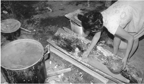 A woman prepares cachiri, an alcoholic drink, in a workshop.
