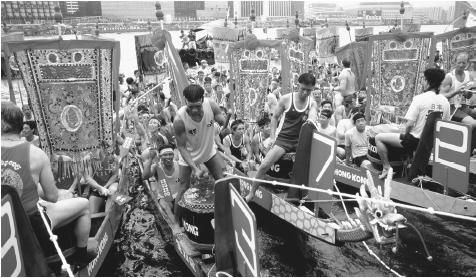 Crew members prepare to race in the Dragon Boat Festival while drummers beat their drums. The Dragon Boat Festival is held annually in June in Hong Kong.