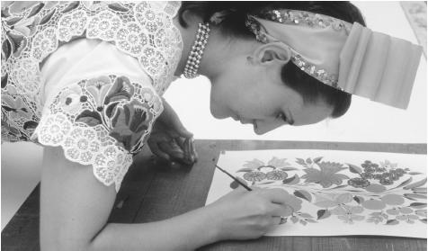 A woman paints a flower design which will be used to make a traditional Hungarian dress in Kalocsa, Hungary.