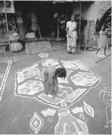 A woman decorates the streets with vibrantly colored rice powder paintings during a festival in Madurai, India.