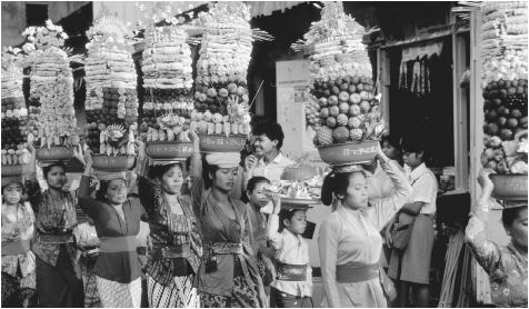 Women carry towering baskets of fruit on their heads for a temple festival in Bali.