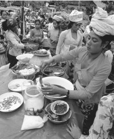 A woman serves food at a market stand. Urban Indonesian women often find work in markets.
