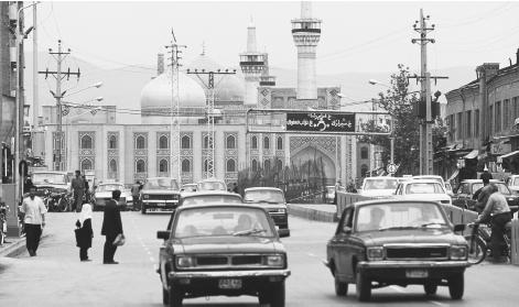 Vehicles travel on a street near the Eman Reza Shrine in Mashhad.