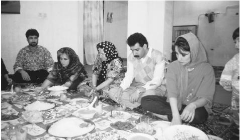 An Iranian family eating a meal in Shiraj. Even after they leave home, members of extended families have hospitality rights in the homes of their most distant relatives.