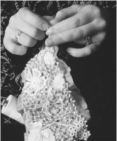 A woman makes clones knots between the main motifs in a piece of hand-crochet.