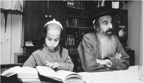 A Torah scribe works with his son. Judaism is the official Israeli religion, and the Torah is the most sacred text.