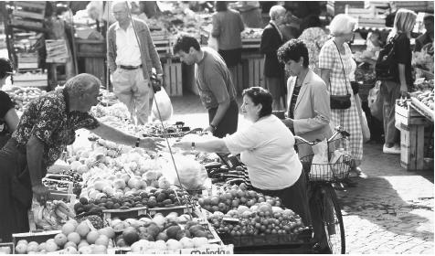 A woman purchases produce at the Campo de Fiori Market in Rome.