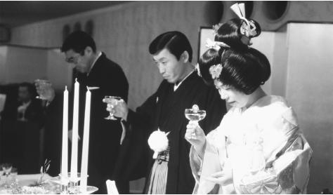A Japanese bride and groom hold their champagne glasses during a traditional Shintō wedding ceremony. Japanese weddings are elaborately staged and usually held in banquet halls or hotels.