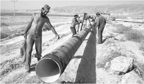 Workmen lay a water pipeline in the Jordan Valley. Most of Jordan is desert.