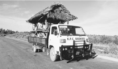 A new home in transit on the back of a truck in Tarawa. Rural houses are built with traditional materials while imported materials are used for homes in towns.