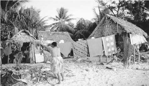 Beach houses in Tarawa, Kiribati, consist of thatched roofs and native wood.
