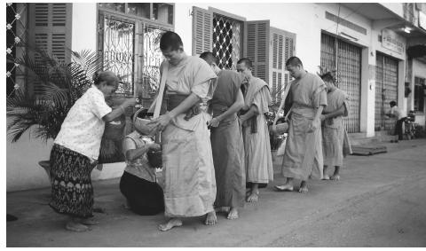 A group of Buddhist monks visit houses at dawn to collect alms in Vientiane.