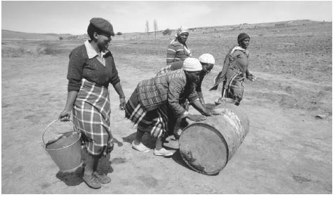 Women roll barrels and carry buckets containing materials needed for the construction of a reservoir.